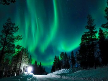 Bright lamp shining on the empty snowy road just as the northern lights appear above the idyllic Scandinavian countryside in the winter. Breathtaking aurora borealis above the calm wintry landscape.