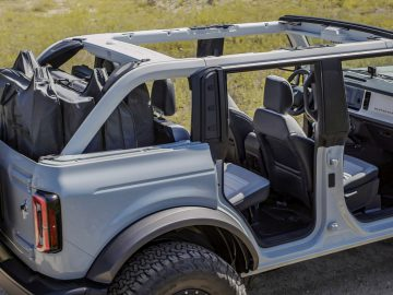 Every Bronco comes with class-exclusive frameless doors that make them easier to remove than what competitors offer. On four-door 2021 Bronco models, all four doors can be stored onboard with protective door bags. Rear quarter windows are also removable, as shown in this four-door Bronco prototype and all will have exclusive cowl-mounted mirrors maintain sideview visibility when the doors are removed. (Prototype not representative of production vehicle.)