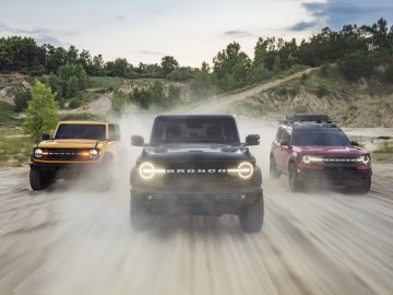 Pre-production versions of the all-new 2021 Bronco family of all-4x4 rugged SUVs, shown here, include (left) Bronco two-door in Cyber Orange Metallic Tri-Coat, Bronco four-door in Shadow Black and Bronco Sport in Rapid Red Metallic Tinted Clearcoat.